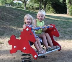 2 enfants sur cheval à bascule
